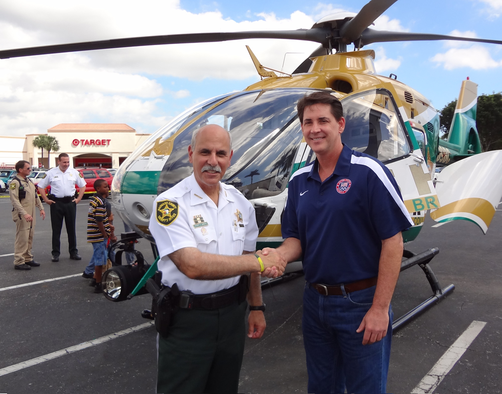 Sheriff Al Lamberti with Mike Nyitray in front of the BSO helicopter.